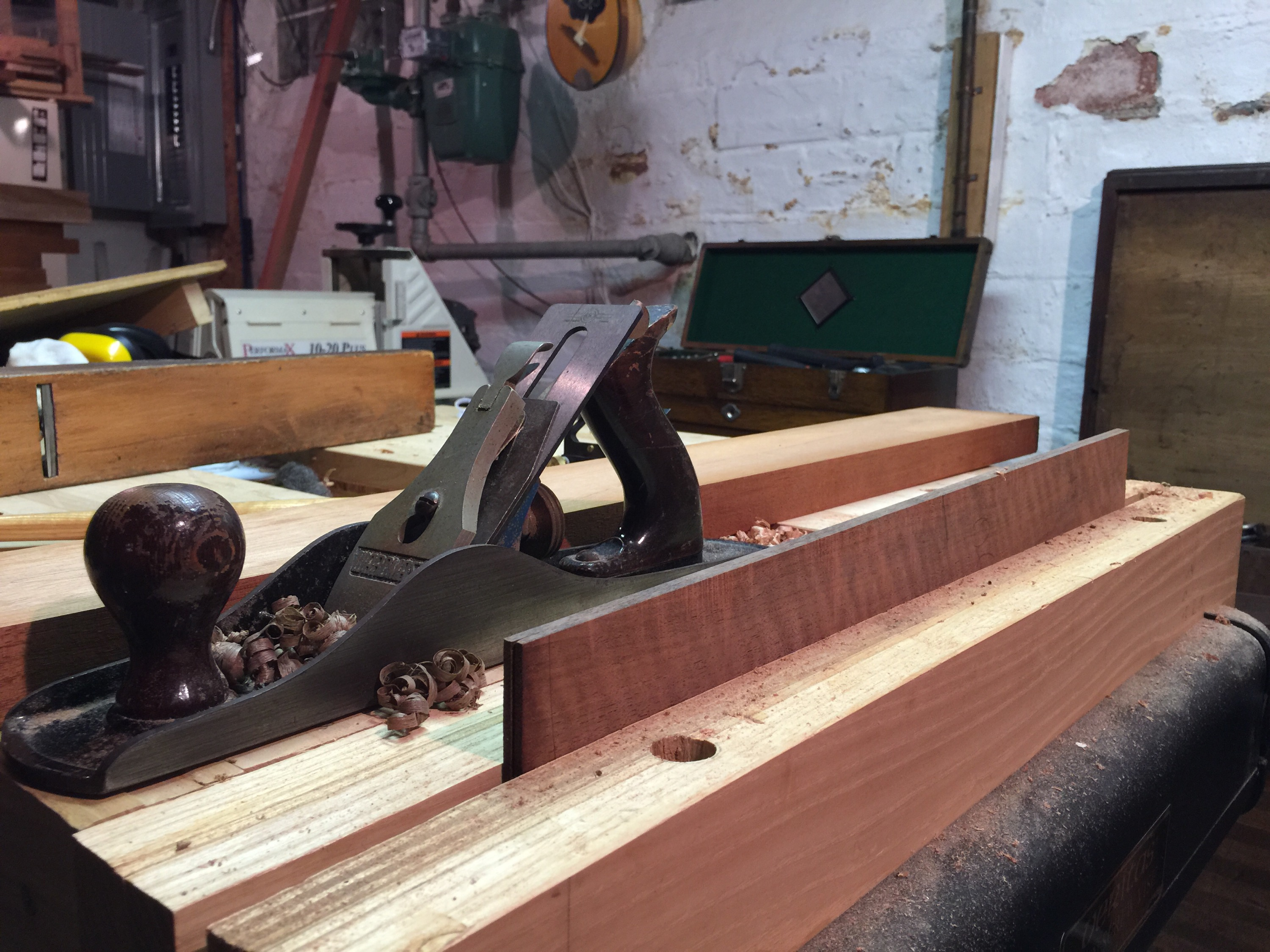 Joining the curly claro walnut back by cutting along the tops of the board with a plane.