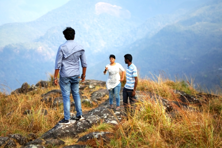 Woman pointing at man on mountain top with another man looking on