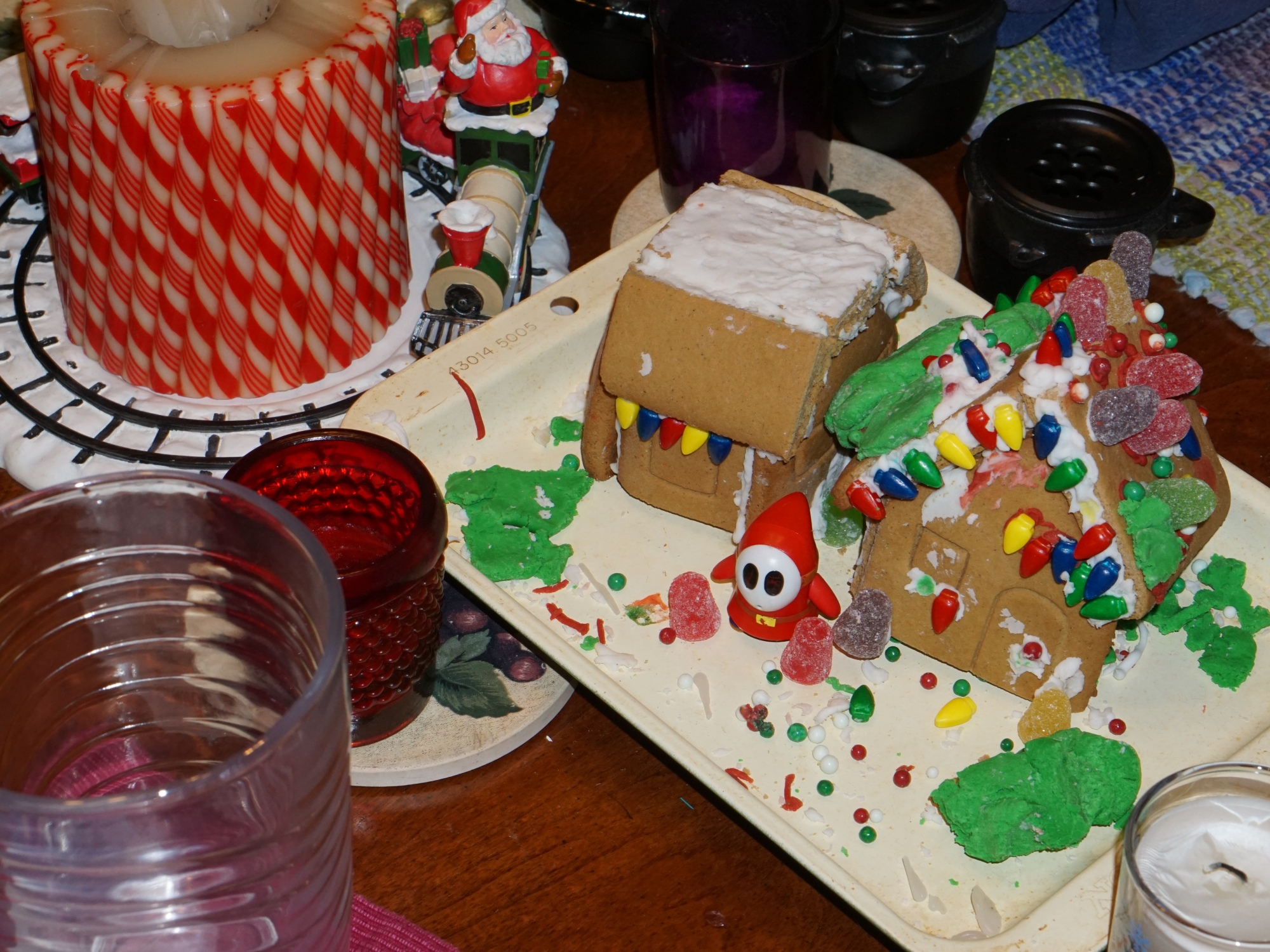 Image of dining room table with gingerbread house centerpiece and candles