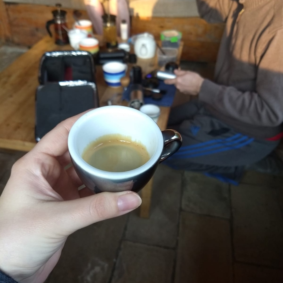 Image of woman's hand holding a cup of espresso in the foreground, man sitting at low table in the background drinking espresso with table full of travel kit of espresso making supplies.