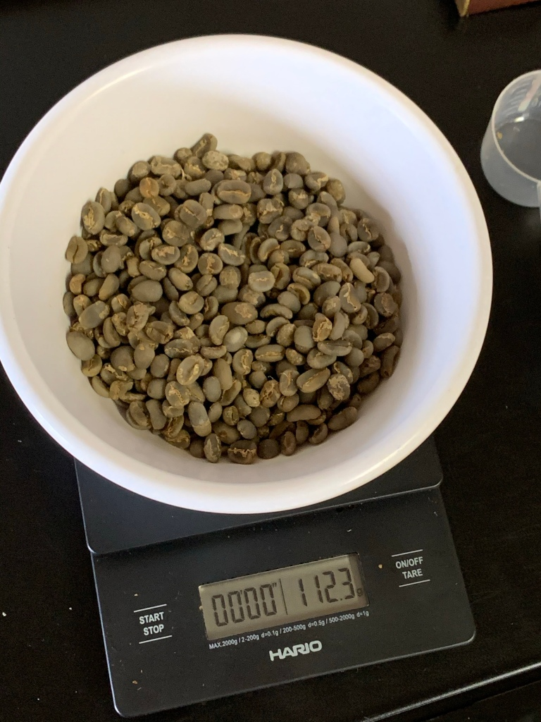 Hario scale with 112.3 grams of green coffee before roasting.