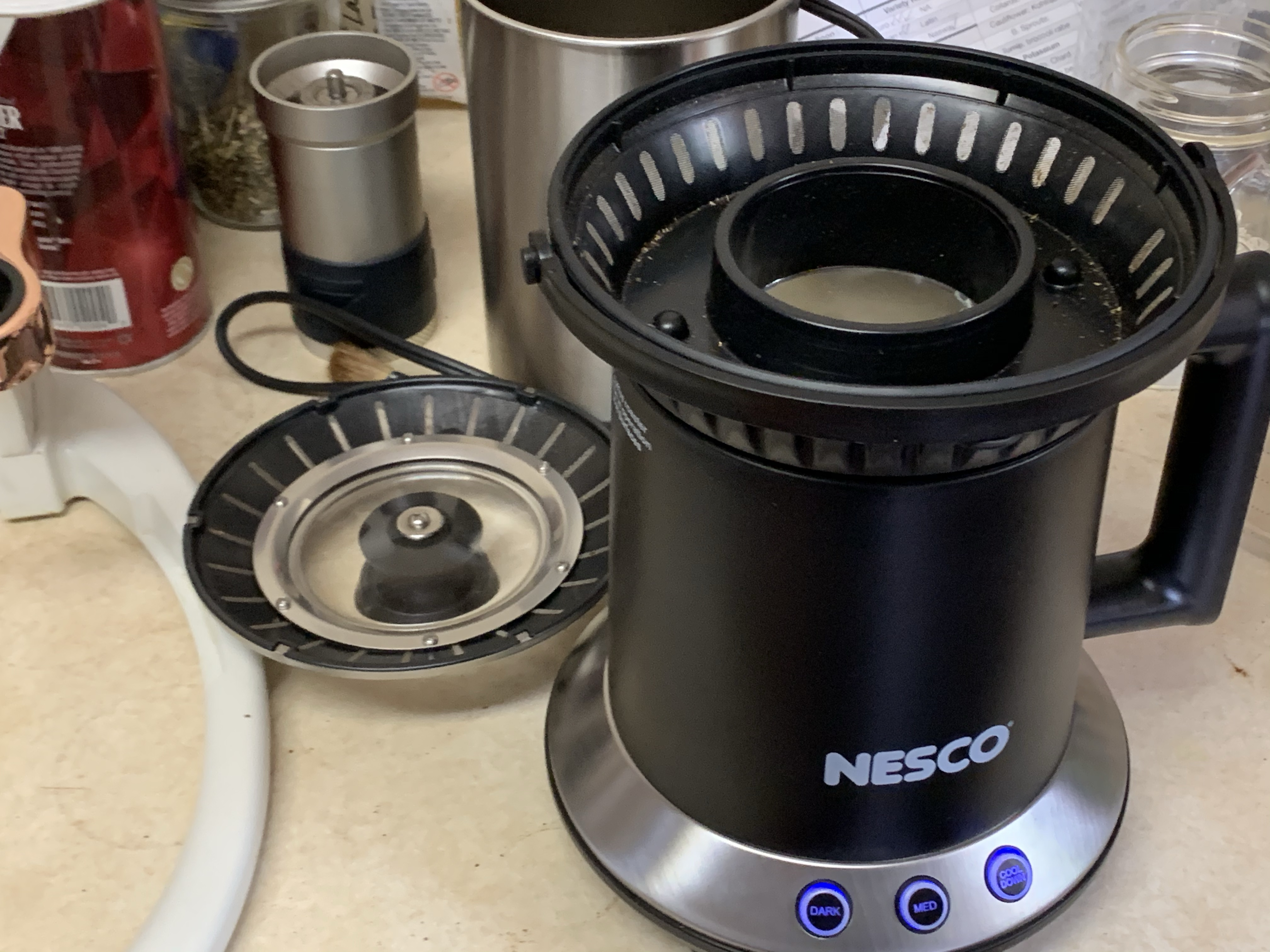 Image of Nesco coffee roaster with lid removed in forground, multiple items in background including Flair Espresso maker, kosher salt shaker, and manual coffee grinder.